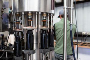 black glass bottles on stainless steel rack