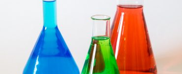 three assorted-color liquid-filled laboratory apparatuses